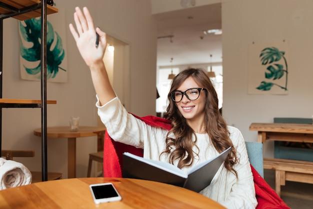 Retrato de uma mulher amigável de óculos, segurando o bloco de notas