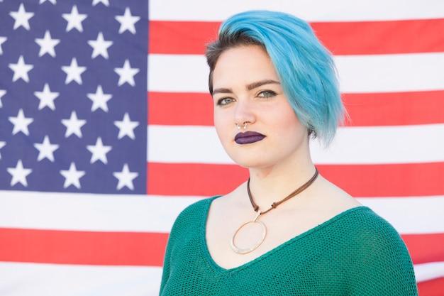 Retrato de uma mulher andrógina lutando pela igualdade contra uma bandeira dos estados unidos da américa