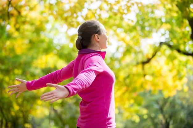 Retrato de uma mulher ao ar livre em uma roupa esportiva, mãos outstreched