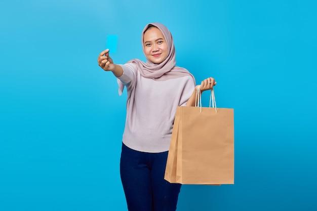 Retrato de uma mulher asiática alegre segurando uma sacola de compras e mostrando o cartão de crédito sobre fundo azul