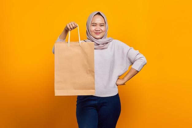 Retrato de uma mulher asiática alegre segurando uma sacola de compras sobre fundo amarelo