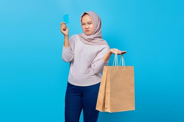 Retrato de uma mulher asiática atraente segurando uma sacola de compras e mostrando o cartão de crédito sobre fundo azul
