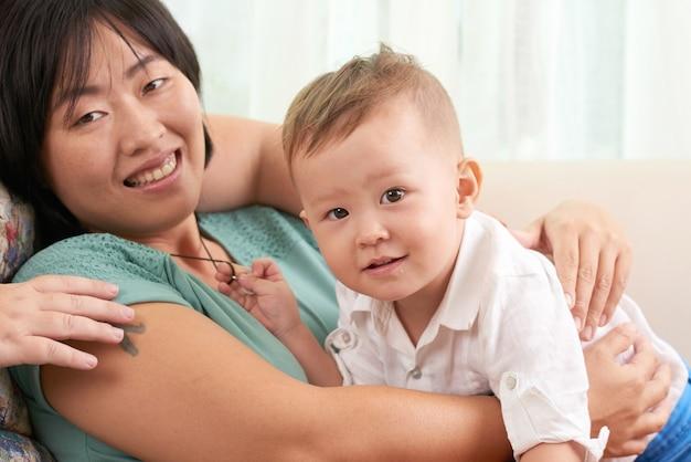 Retrato de uma mulher asiática bonita com seu filho sorrindo enquanto descansa no sofá