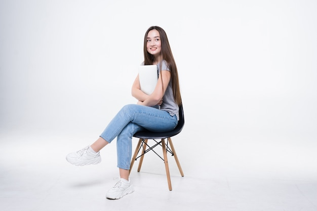 Retrato de uma mulher asiática casual feliz segurando um laptop enquanto está sentado em uma cadeira sobre uma parede branca