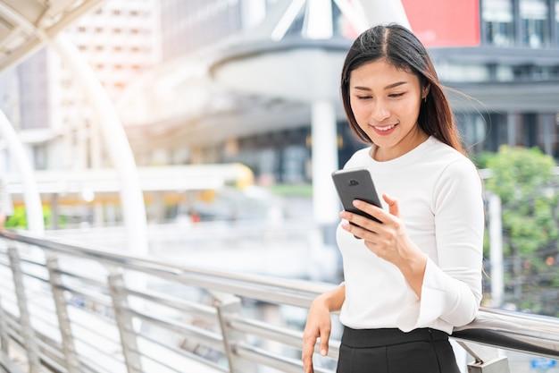 Retrato de uma mulher asiática casual sorridente segurando o smartphone para comunicação na cidade