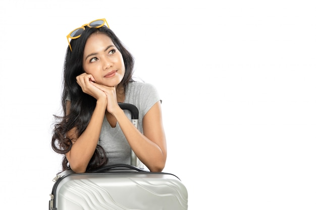Retrato de uma mulher asiática com roupas de verão em pé com uma mala. ela pensou e olhou para o espaço da cópia ao lado. isolado em fundo branco