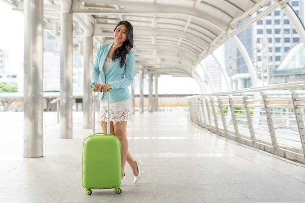 Retrato de uma mulher asiática de negócios viajando com uma bagagem, linda linda garota vestindo roupas de mulher de negócios no fundo urbano da cidade de distrito comercial, conceito de negócio