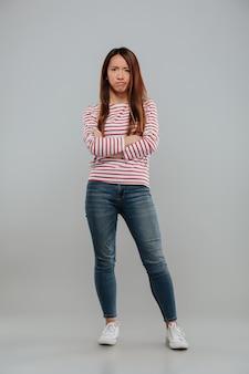 Retrato de uma mulher asiática decepcionada em pé com os braços cruzados