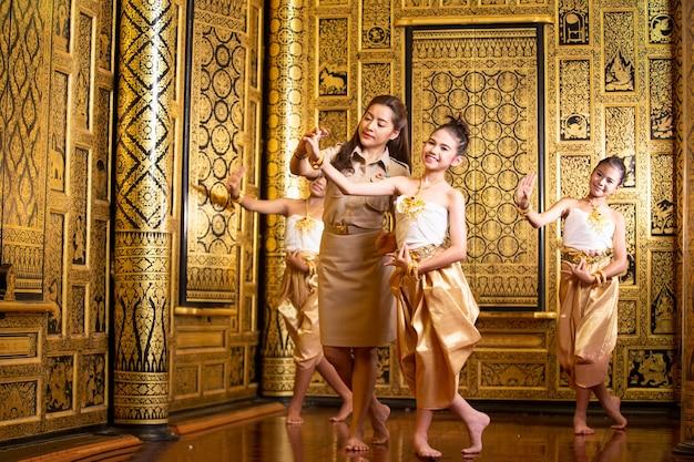 Retrato de uma mulher asiática em dançarina tradicional tailandesa as roupas estão dançando no templo de buda.