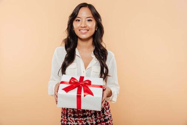 Retrato de uma mulher asiática feliz mostrando a caixa de presente