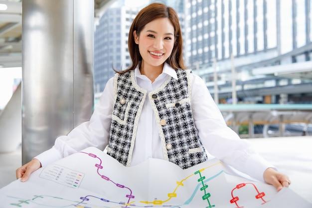 Retrato de uma mulher asiática jovem adulta sorridente fofa em roupas da moda casual preto e branco inteligente, encostado no mastro, segurando um mapa do metrô em papel e olhando para a câmera com um fundo desfocado