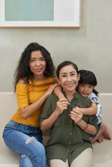 Retrato de uma mulher asiática madura e alegre abraçada pela filha adulta e pela neta fofa sentada no sofá