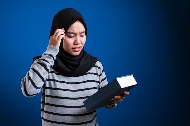 Retrato de uma mulher asiática muçulmana fofa, doente e cansada de ler muitos livros sobre o fundo azul