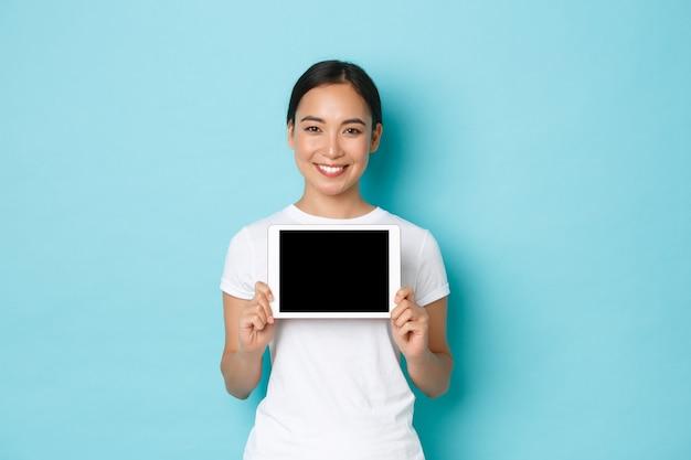 Retrato de uma mulher asiática muito sorridente mostrando a tela do tablet digital com expressão satisfeita, demonstração do site de compras, aplicativo para artista, parede azul clara em pé