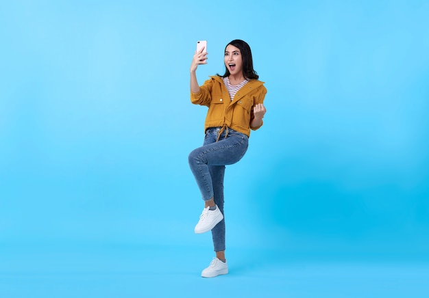 Retrato de uma mulher asiática nova feliz que comemora com o telefone móvel isolado sobre o fundo azul.