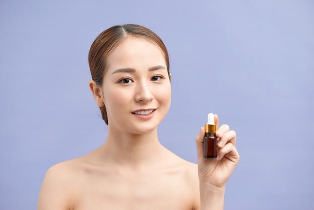 Retrato de uma mulher asiática saudável e sorridente segurando um recipiente de cosméticos