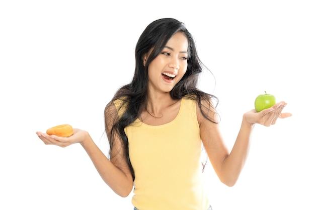 Retrato de uma mulher asiática segurando uma maçã verde e um donut com as duas mãos