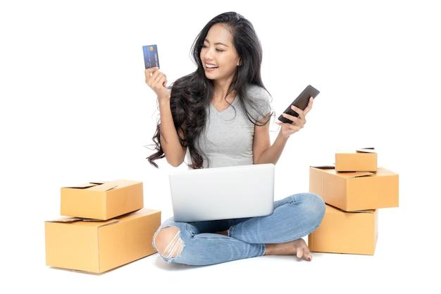 Retrato de uma mulher asiática sentada no chão com um monte de caixas ao lado.