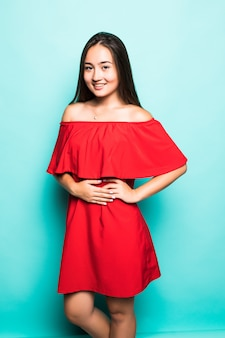 Retrato de uma mulher asiática sorridente no vestido vermelho em pé olhando para a câmera isolada sobre fundo turquesa