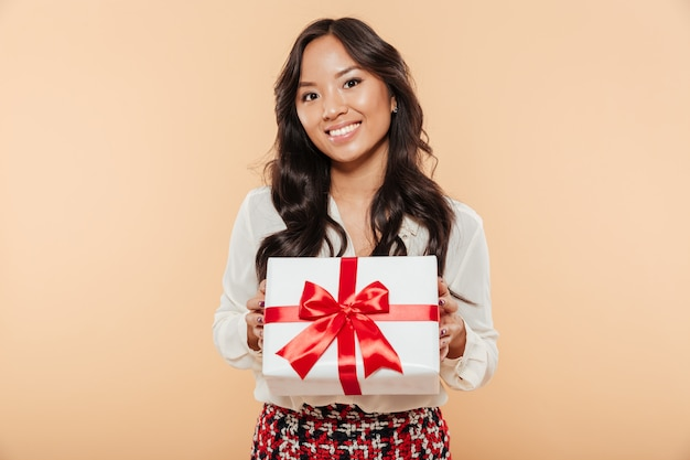 Retrato de uma mulher asiática sorridente segurando a caixa de presente