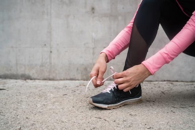 Retrato de uma mulher atlética amarrando os cadarços e se preparando para correr ao ar livre. esporte e conceito de estilo de vida saudável.