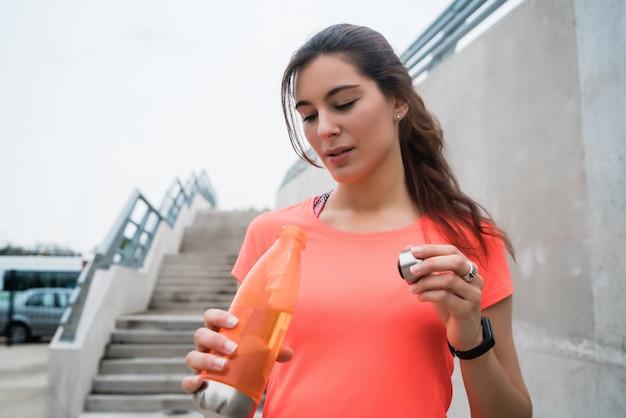 Retrato de uma mulher atlética bebendo água após o treino. conceito de estilo de vida de esporte e saúde.