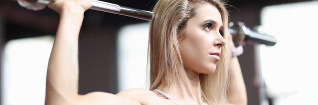 Retrato de uma mulher atlética fazendo flexões na barra horizontal do conceito