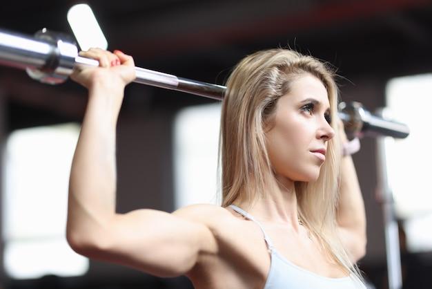 Retrato de uma mulher atlética fazendo flexões no bar
