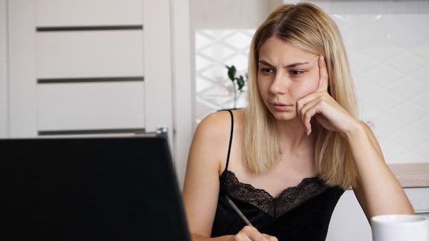 Retrato de uma mulher atraente à mesa com xícara e laptop. mulher jovem confusa tendo problemas com o computador, olhando para a tela do laptop