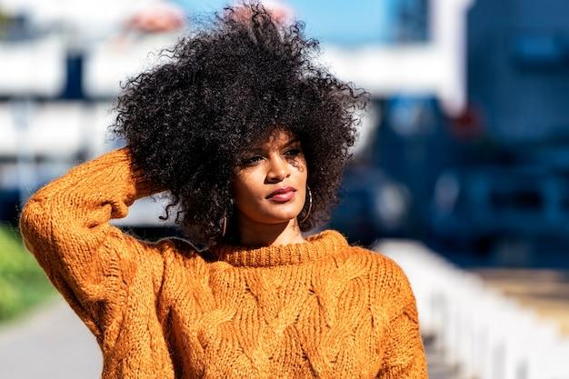 Retrato de uma mulher atraente afro na rua. conceito de estilo de cabelo