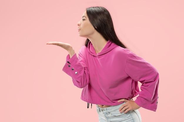 Retrato de uma mulher atraente com beijo na boca. estúdio rosa.