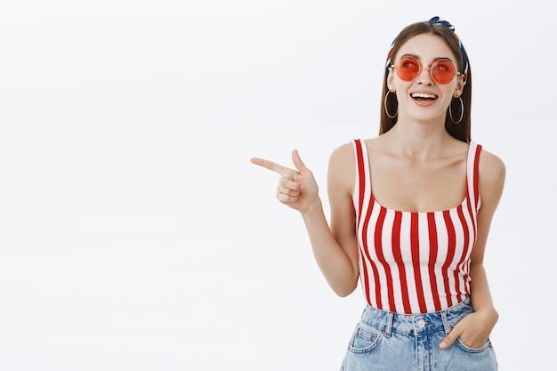 Retrato de uma mulher atraente, criativa e elegante, interessada em um top listrado e óculos de sol vermelhos, segurando a mão no bolso, casualmente, apontando e olhando para a esquerda com um sorriso largo e entusiasmado, vendo o espaço da cópia curioso