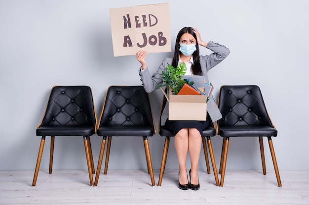 Retrato de uma mulher atraente, desesperada e desempregada, gerente executiva sentada na cadeira, segurando nas mãos, pôster, palavras de emprego, pertences, usar máscara de gaze mers cov isolado fundo de cor cinza pastel