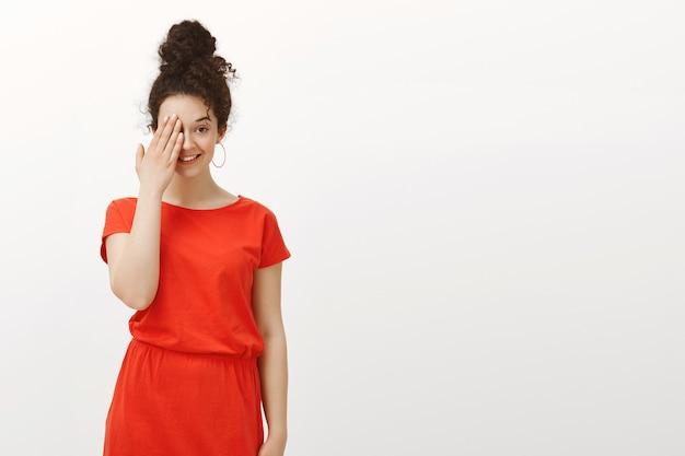 Retrato de uma mulher atraente e atraente em um lindo vestido vermelho, cobrindo metade do rosto com a palma da mão e sorrindo amplamente