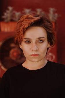 Retrato de uma mulher atraente e atrevida com cabelo curto ruivo no quintal da cidade velha com paredes vermelhas