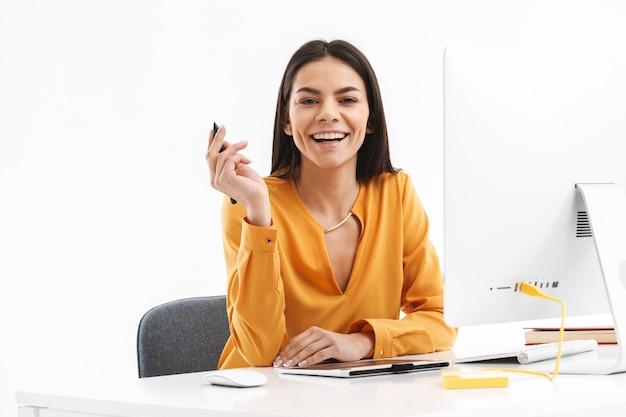 Retrato de uma mulher atraente e jovem designer usando computador tablet gráfico e caneta stylus enquanto trabalhava em um escritório bem iluminado