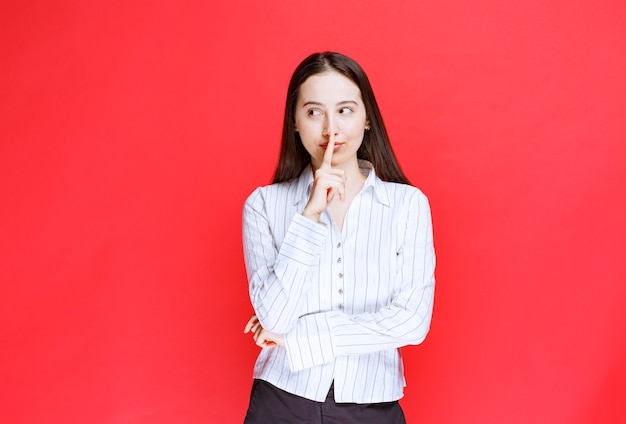 Retrato de uma mulher atraente em pé e fazendo sinal silencioso.