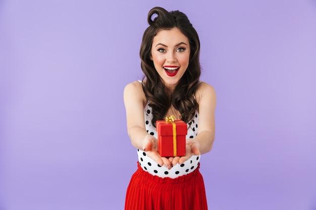 Retrato de uma mulher atraente em um vestido vintage de bolinhas, sorrindo enquanto segura uma caixa de presente vermelha isolada sobre a parede violeta