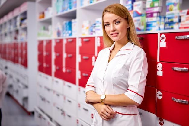 Retrato de uma mulher atraente farmacêutica perto de prateleiras com medicamentos