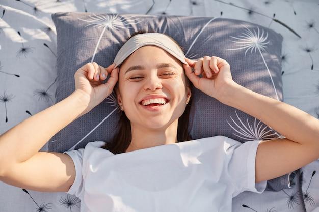 Retrato de uma mulher atraente feliz acordando no campo, tira a máscara de dormir de seus olhos e rindo, desfrutando de um descanso em um prado verde, expressando felicidade.