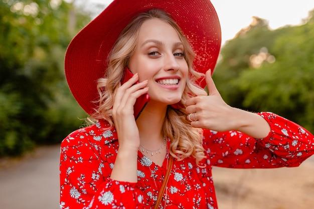 Retrato de uma mulher atraente loira elegante sorridente com chapéu de palha vermelho e blusa roupa da moda de verão falando no telefone emoção de gesto positivo