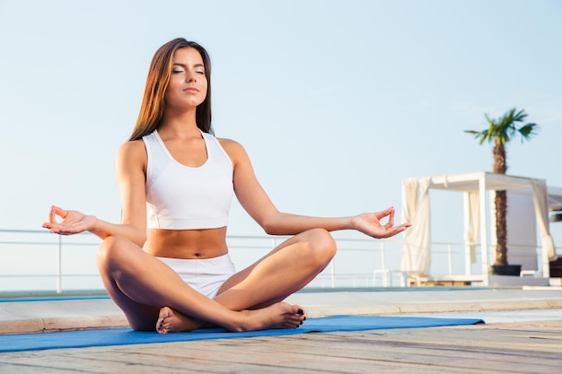 Retrato de uma mulher atraente meditando ao ar livre