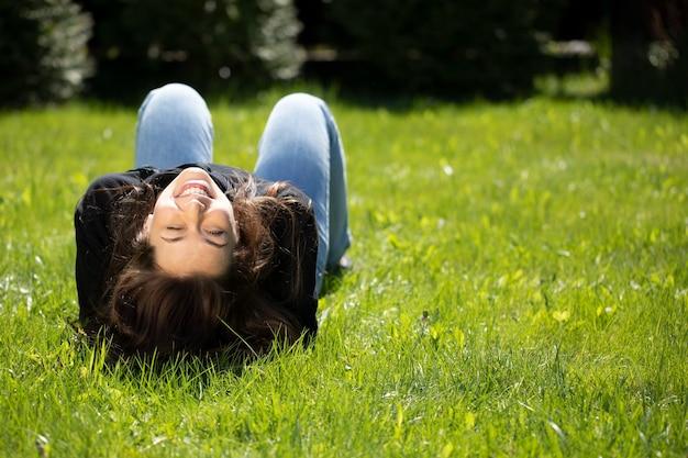 Retrato de uma mulher atraente morena com cabelos longos, vestida com um capuz preto deitada na grama verde
