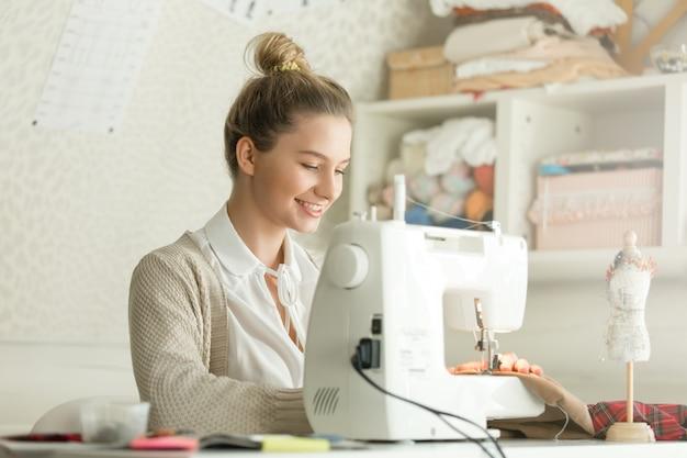 Retrato de uma mulher atraente na máquina de costura
