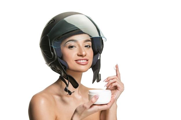 Retrato de uma mulher atraente no capacete de moto em fundo branco do estúdio. conceito de beleza, proteção para pele e rosto