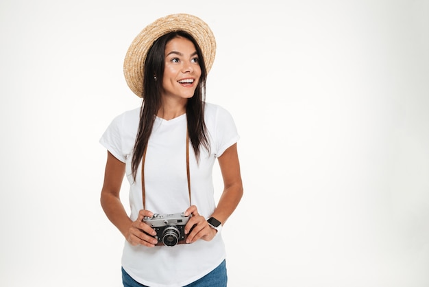 Retrato de uma mulher atraente no chapéu segurando uma câmera