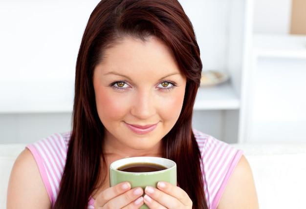 Retrato de uma mulher atraente segurando uma xícara de café em casa