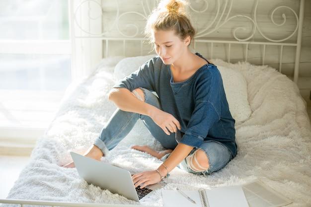 Retrato de uma mulher atraente sentada na cama com laptop