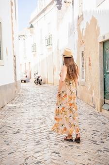 Retrato de uma mulher atraente turista na cidade velha, usando um elegante vestido longo, pulseiras e chapéu de palha.