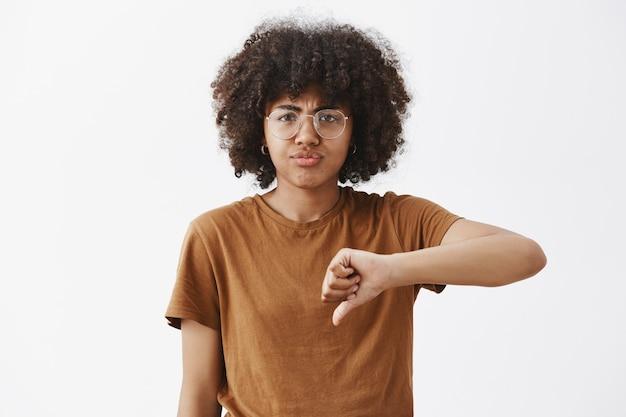 Retrato de uma mulher bonita afro-americana, descontente e impressionada, com um penteado afro, mostrando os polegares para baixo e amuando-se de decepção